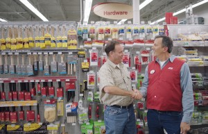Ace associate and customer shaking hands in the paint aisle of an Ace Hardware store.