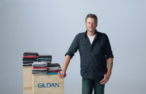 Country music start Blake Shelton leaning against crates of Gildan underwear.